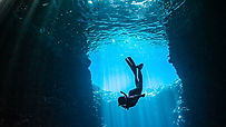 Girl diving in cavern with lightbeams co