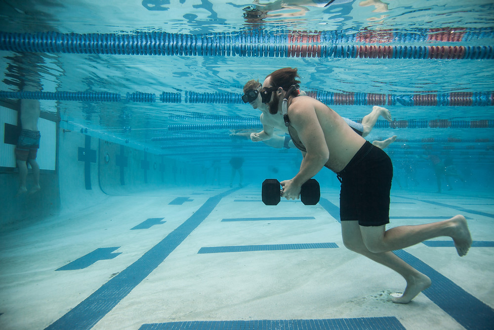 A Voyage Recovery patient carries a 40lb weight in our rock-walking exercise while his teammate lends support