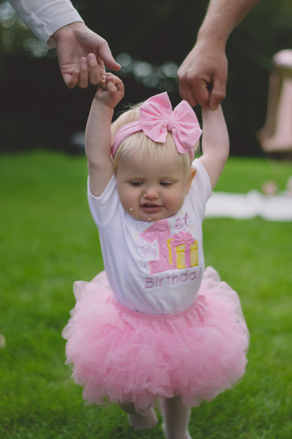 first birthday girl walks holding mum and dads hands