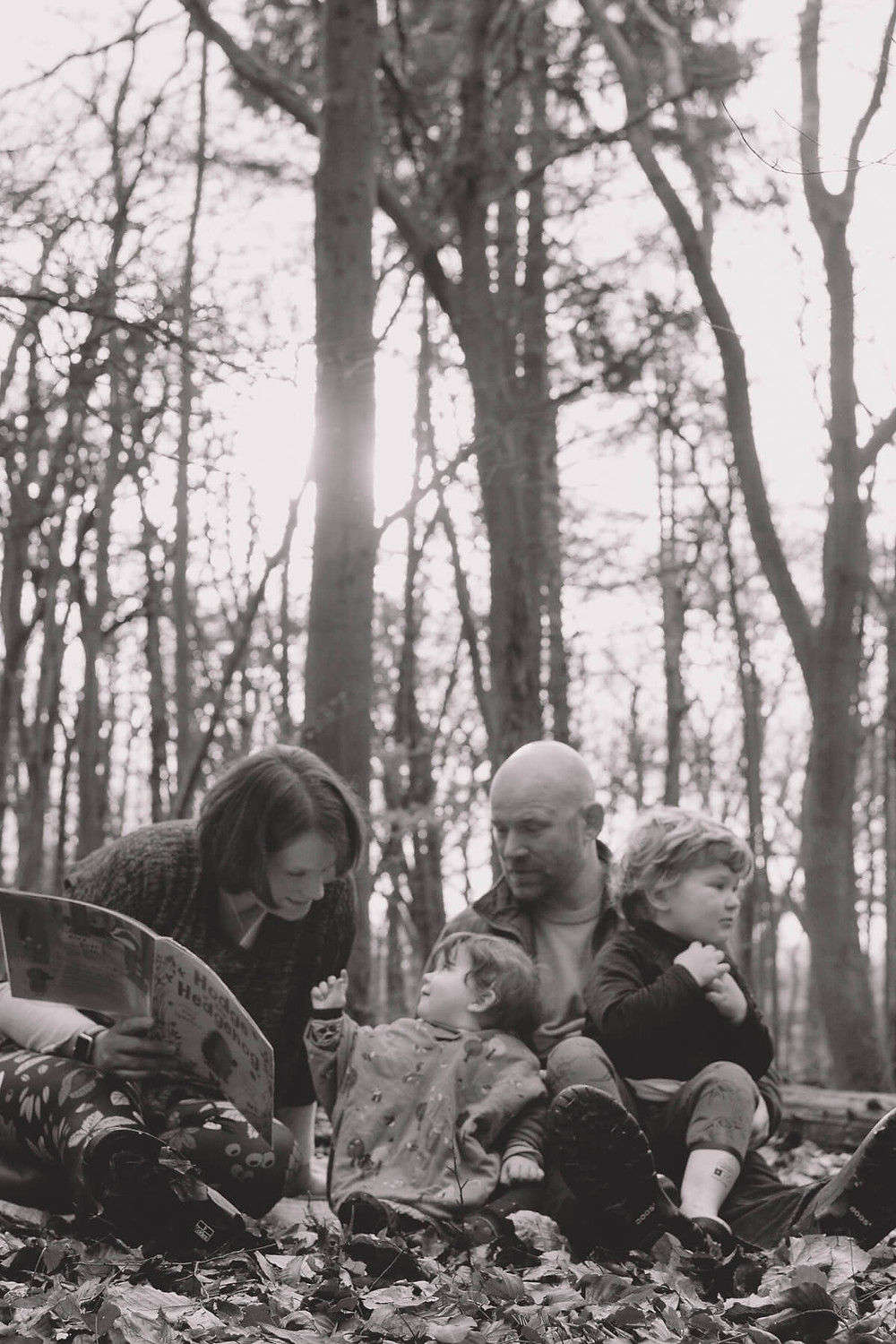 family playing reading in forest sunny autumn black white