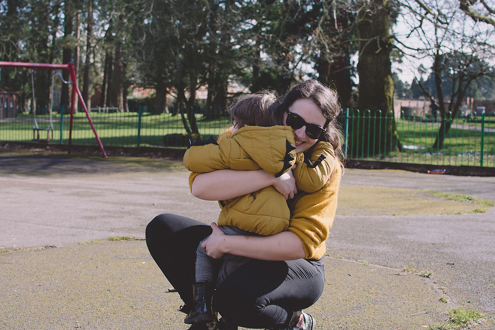 woman smiles hugging son on park
