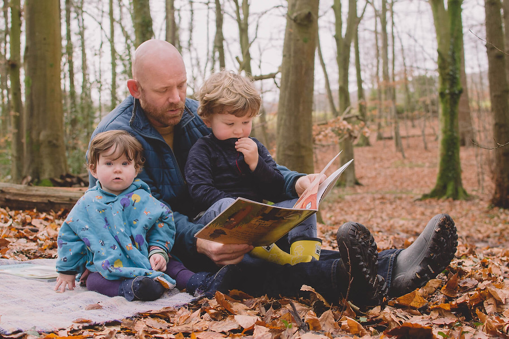 dad reading book to children son on lap in forest