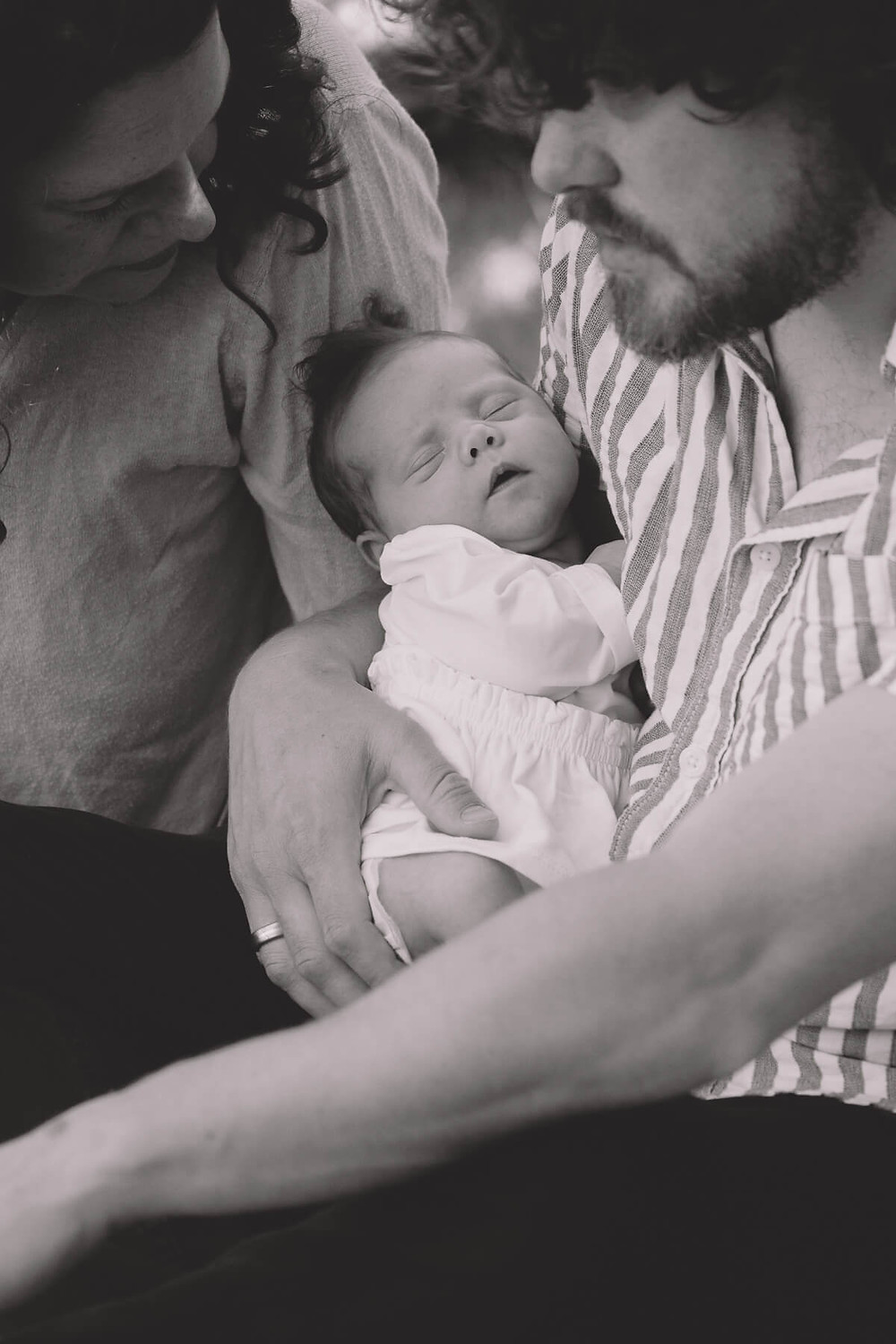 newborn baby sleeping in dads arms black and white