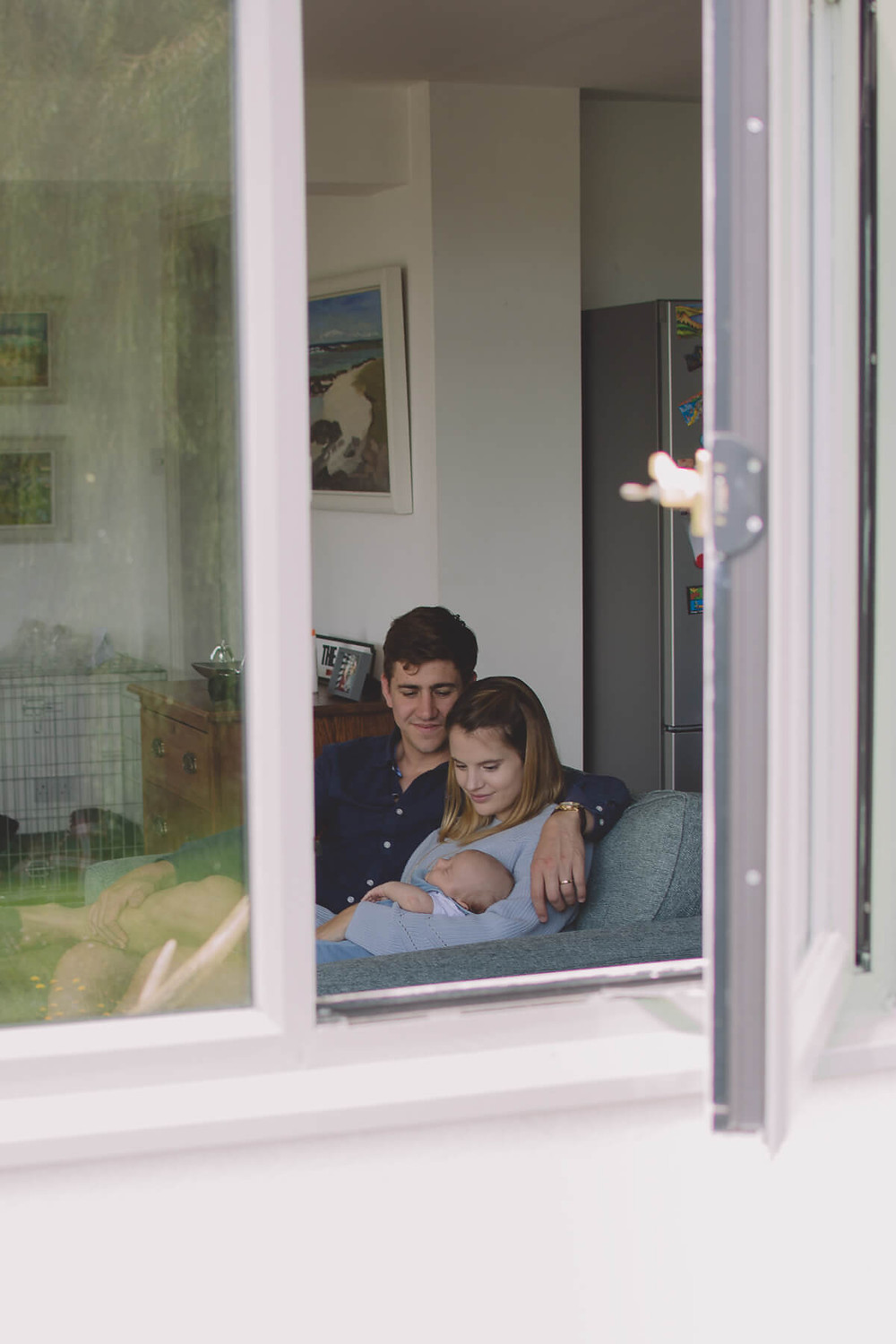 looking through open window family with newborn baby