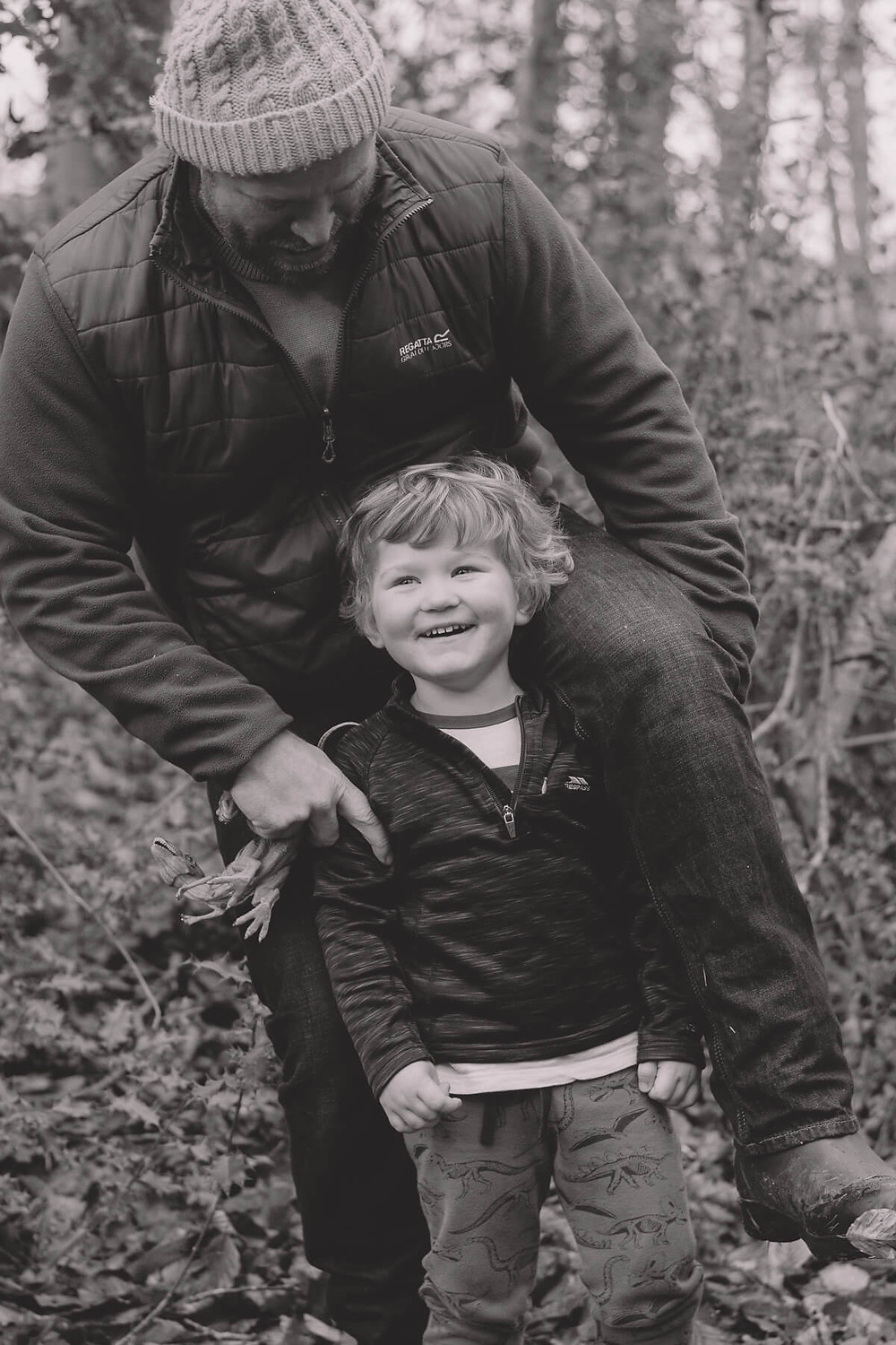 dad playing with son in forest climbing onto shoulders