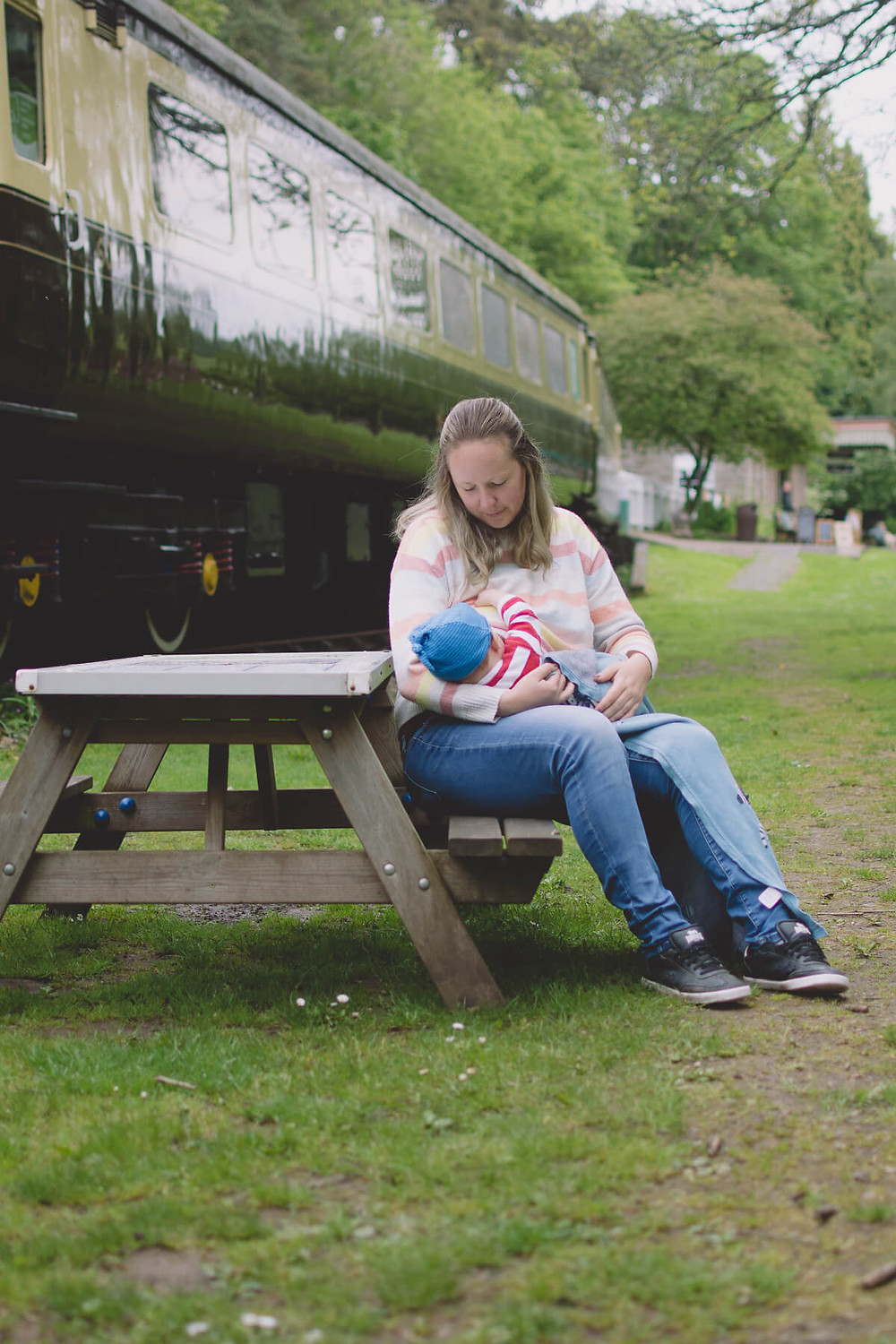 mother sits at picnic table breastfeeding baby outside