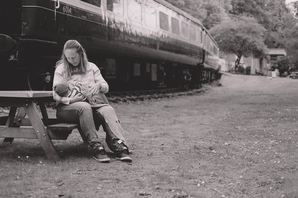 mother sits in front of old train breastfeeding baby