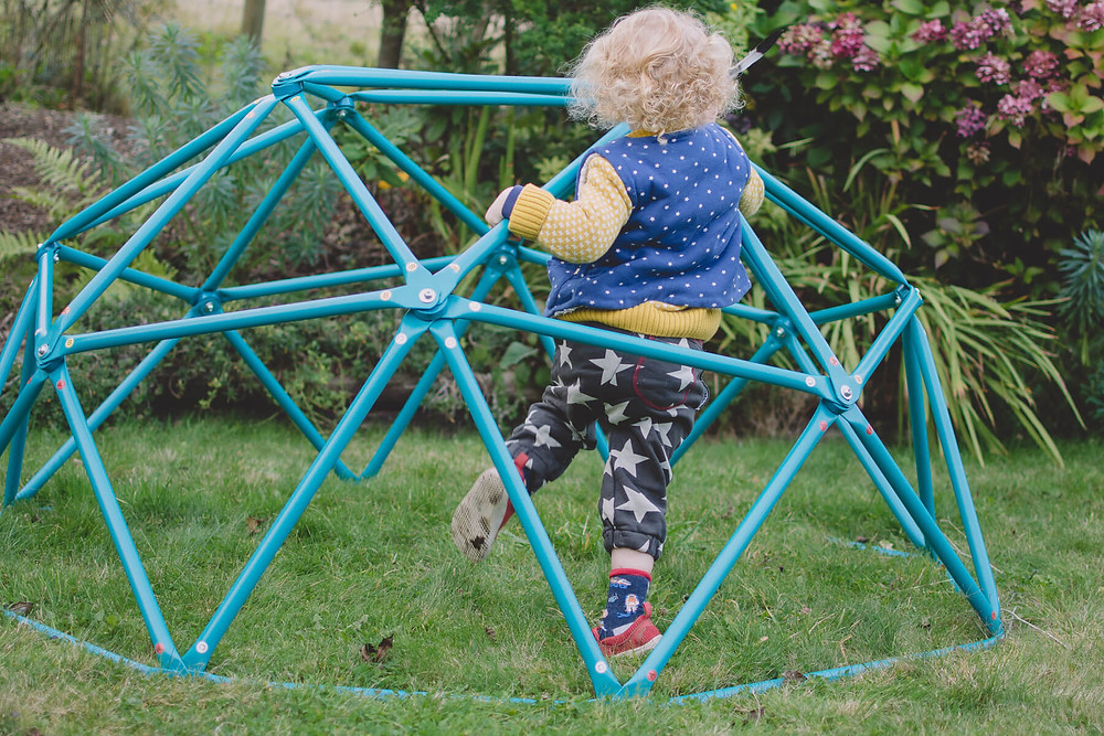 toddler playing on climbing frame