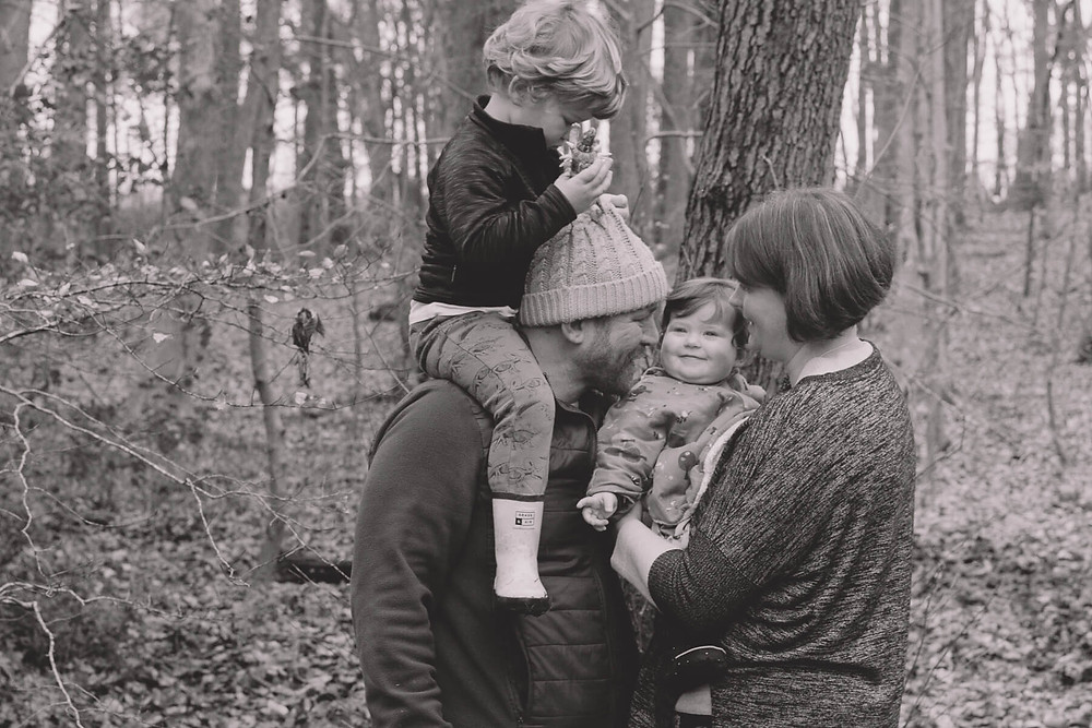 family playing in forest baby girl big smile black and white