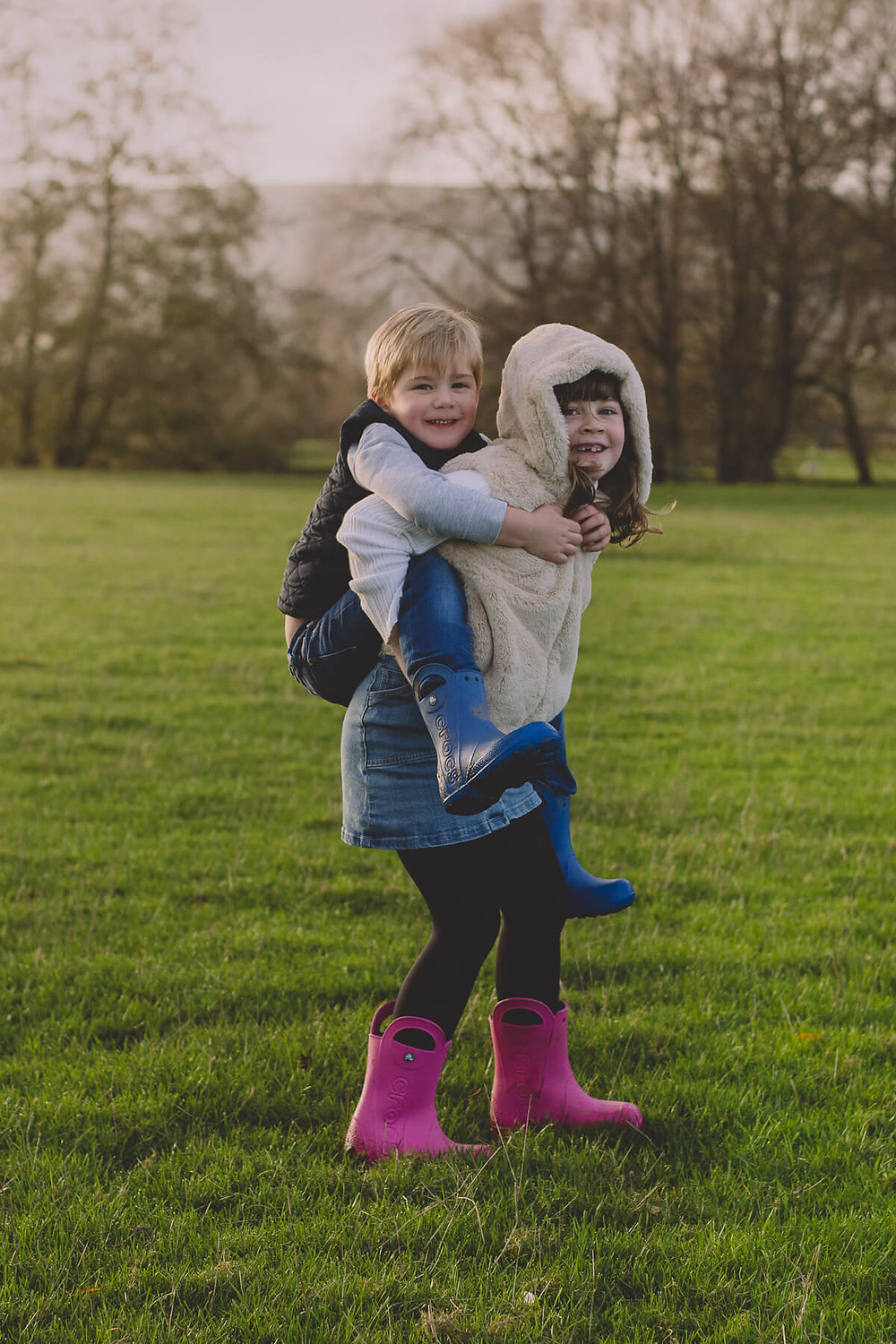 boy getting piggy back from big sister running playing smile