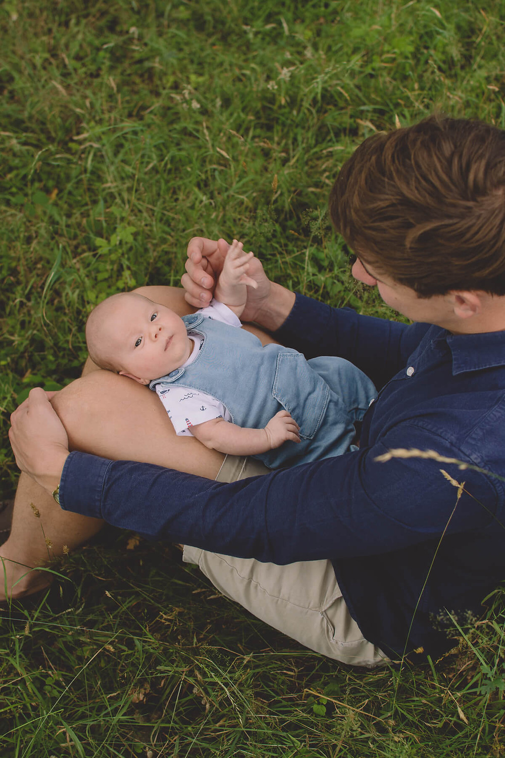 young father newborn baby on his lap sitting in grass
