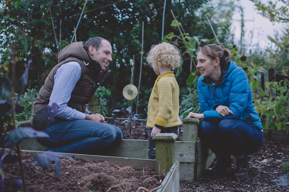 family smiling playing in vegetable garden