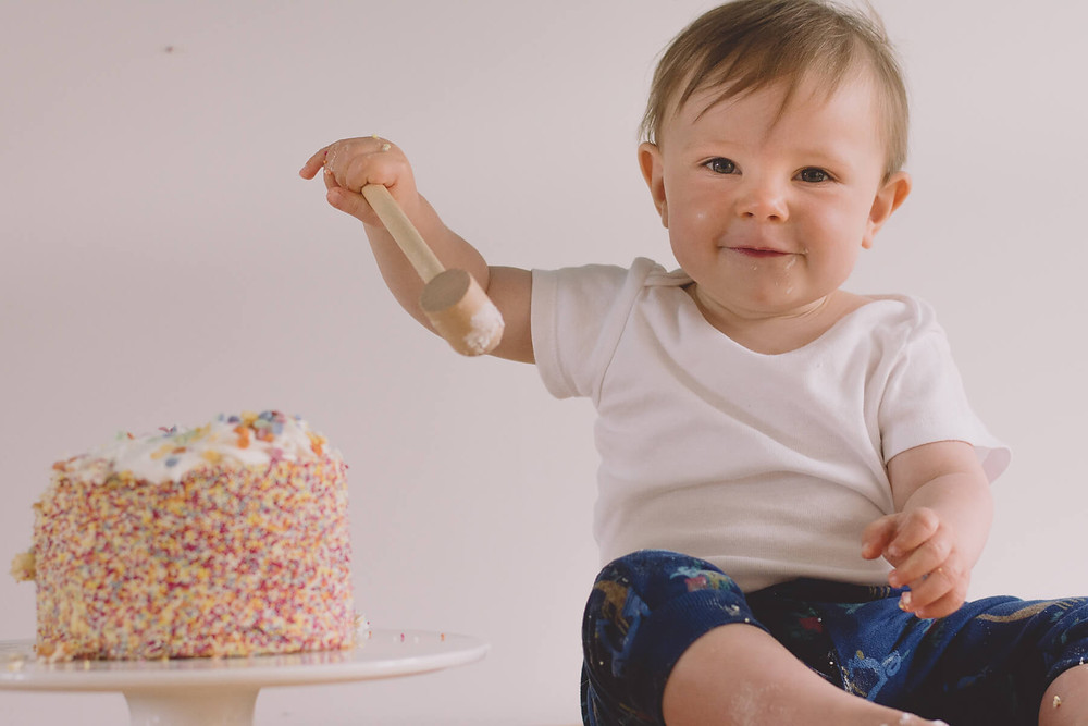 cake smash photo shoot smiling toddler with toy