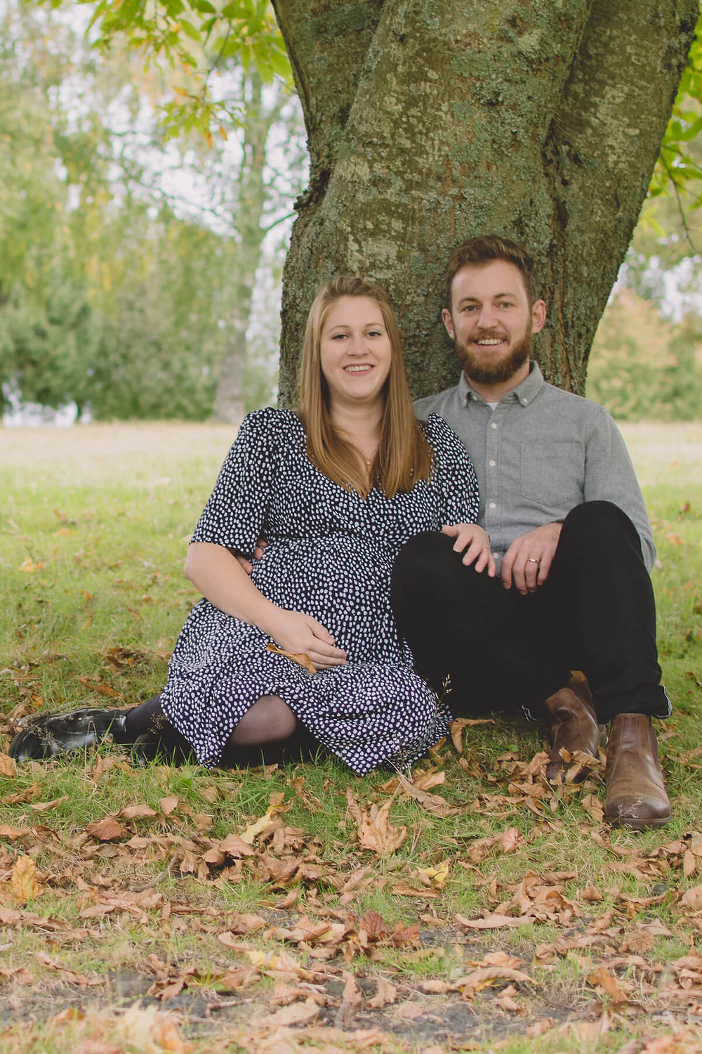 pregnant couple sit under tree