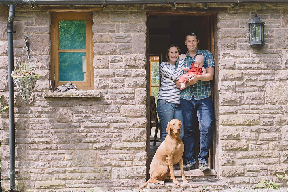 couple stand in doorway dad hold newborn baby dog sat close