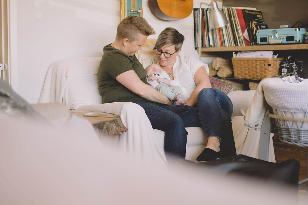 same sex couple sitting with newborn daughter south wales