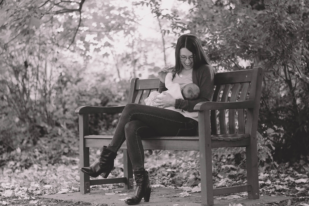 black and white woman sitting on bench feeding baby