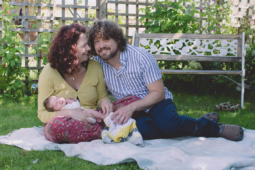 husband and wife sitting in garden with newborn daughter