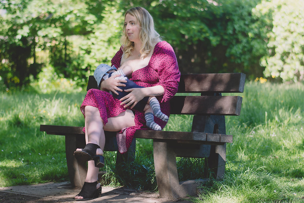 mother breastfeeding in park on bench baby south wales