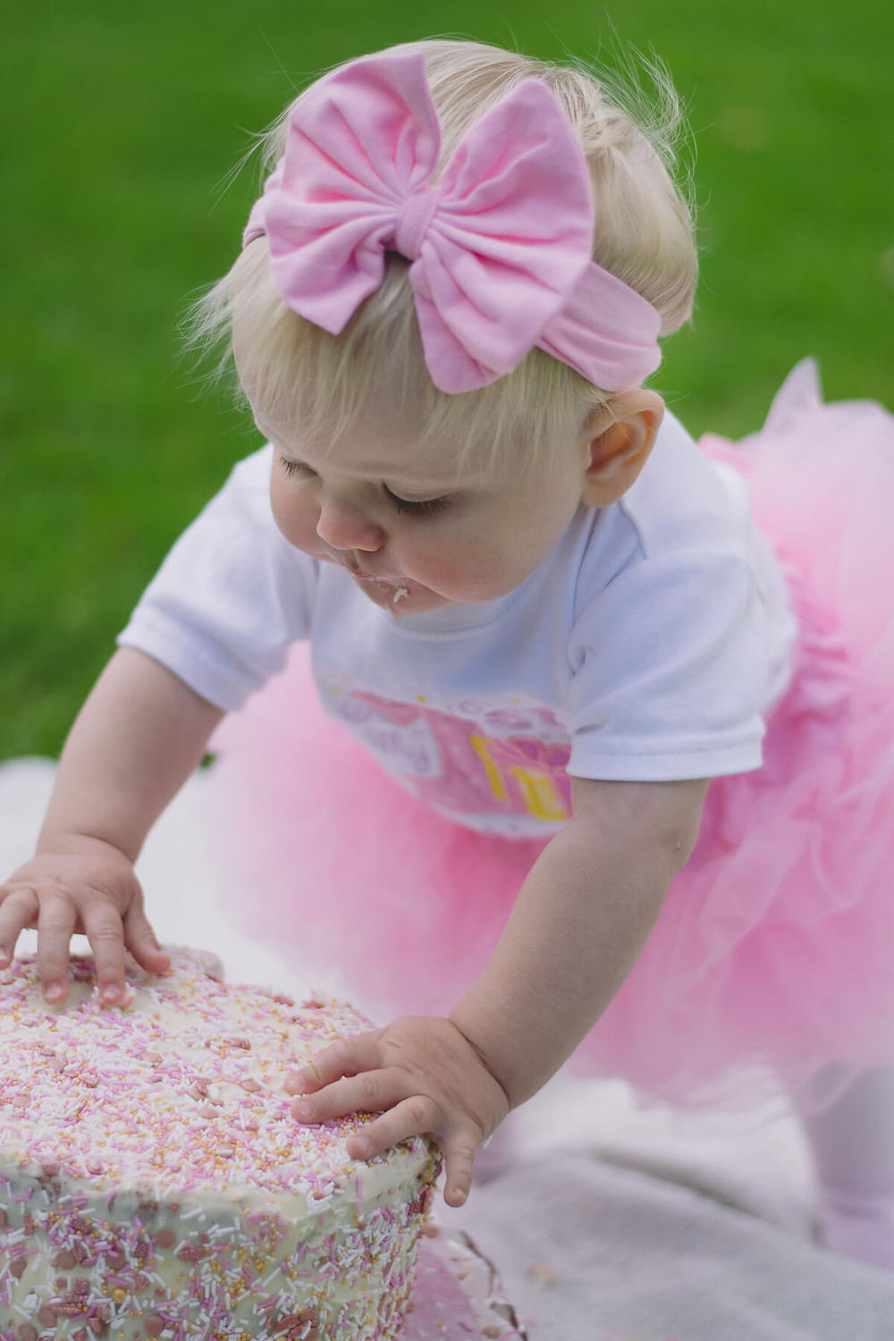 birthday girl in tutu with sprinkle cake grabbing with hands