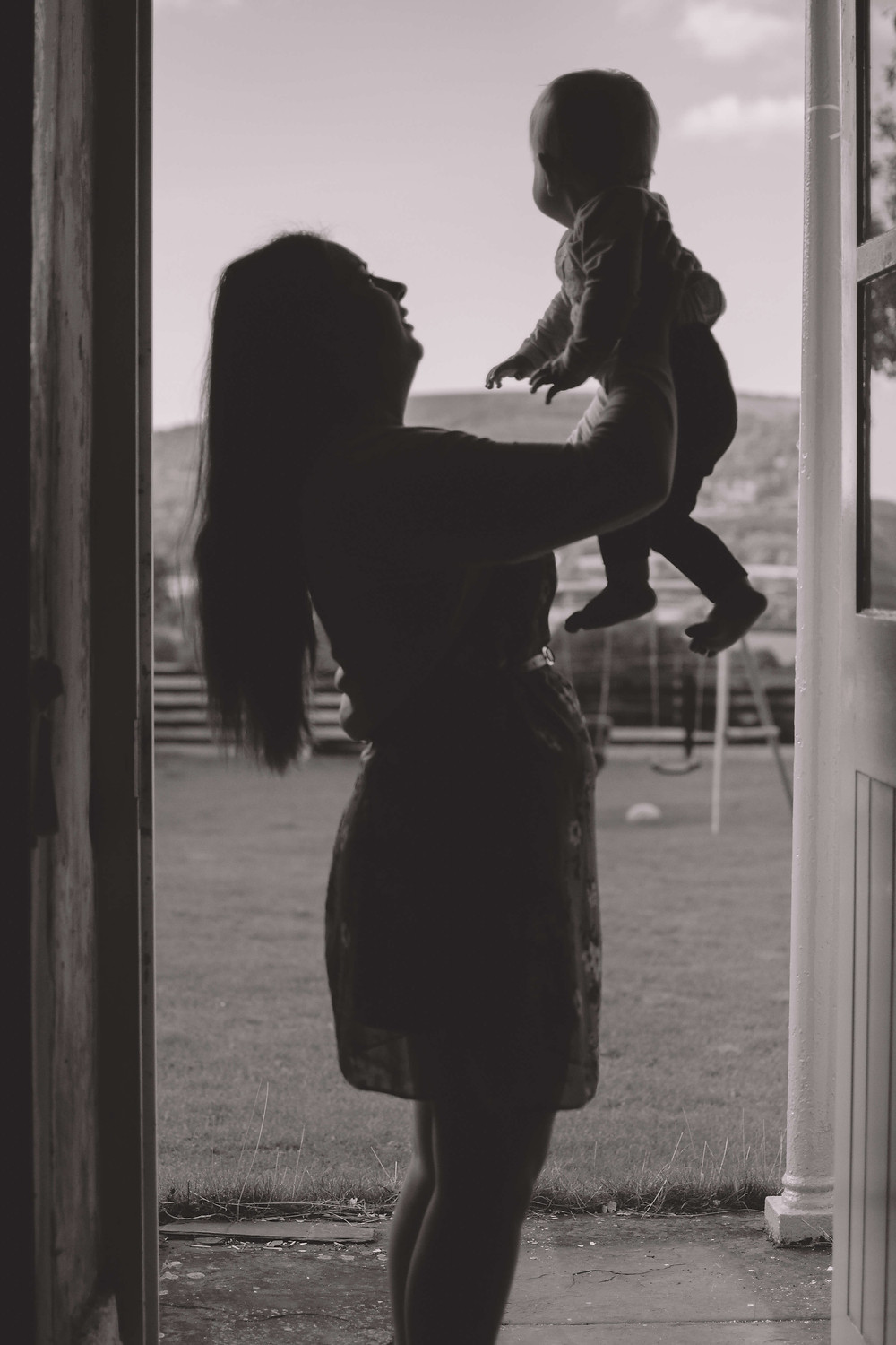 mother and younger daughter play in doorway