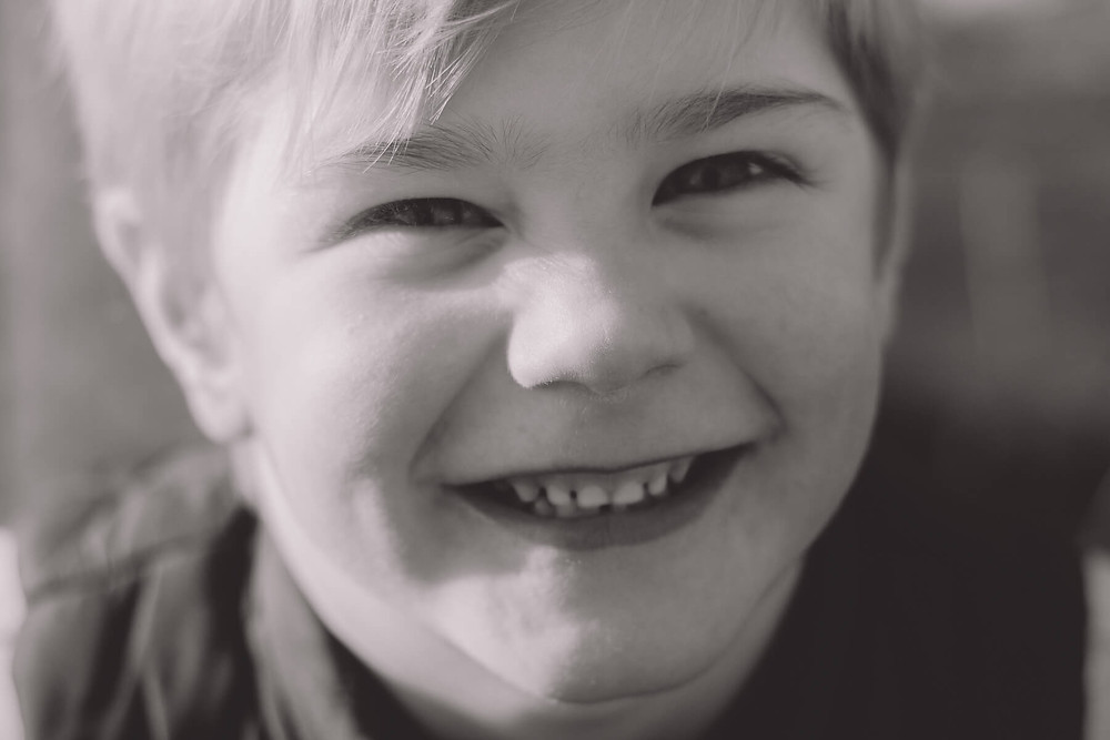 black and white close up of boys smiling face