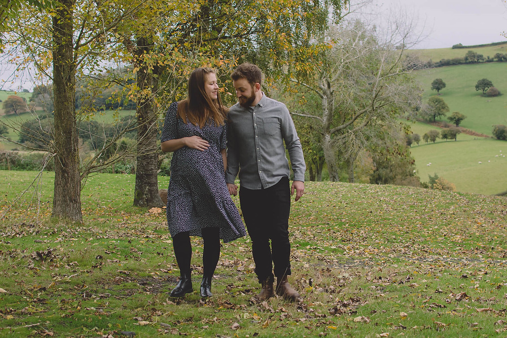 husband and pregnant wife walk through field