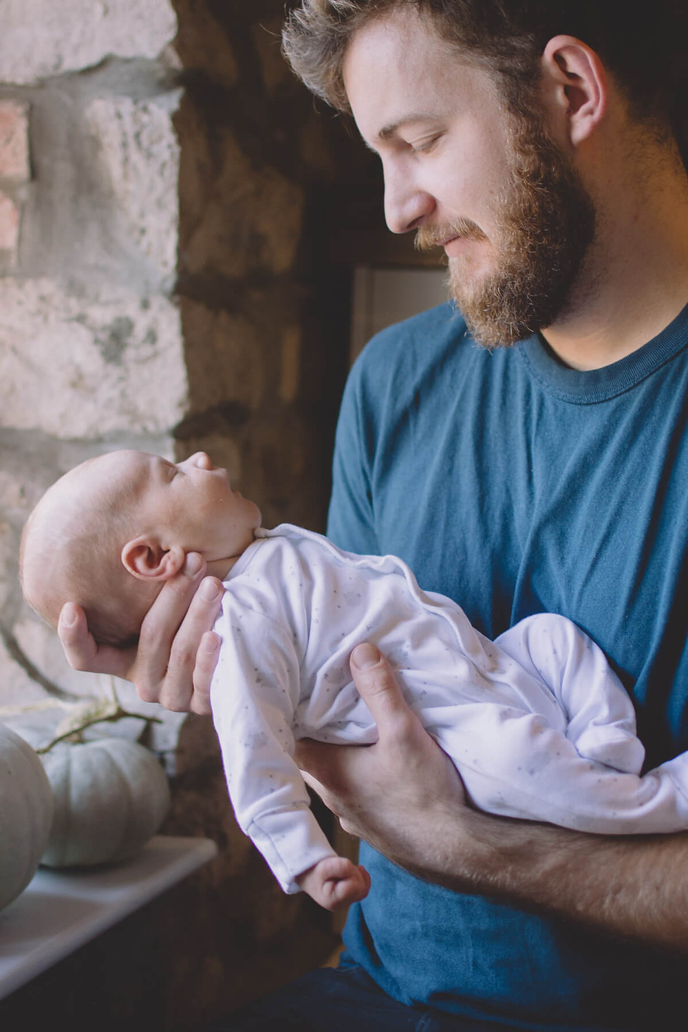 sleeping baby held by smiling dad newborn photography wales