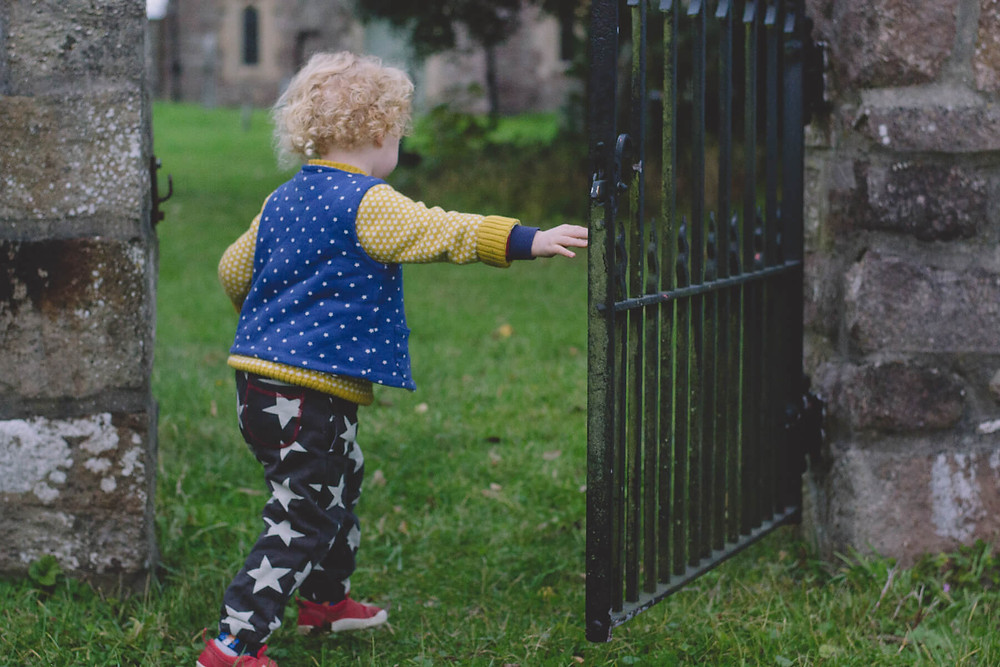 child walking through iron gate
