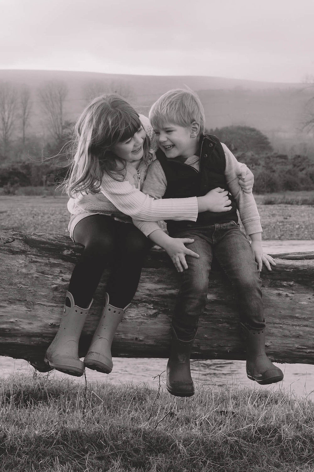 black and white young brother and sister laugh hug sat on log