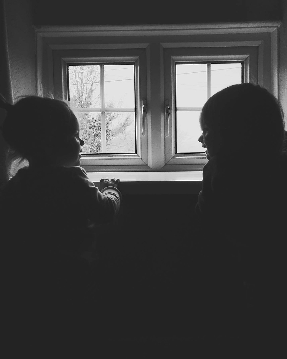 two young children smile by window