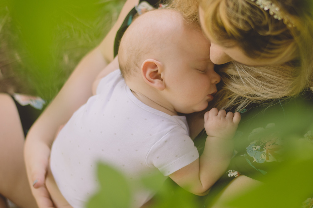 newborn baby sleeping on mums chest outside framed by leaves