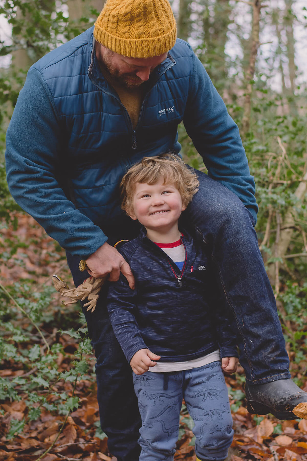 dad playing with smiling son in forest climbing shoulders
