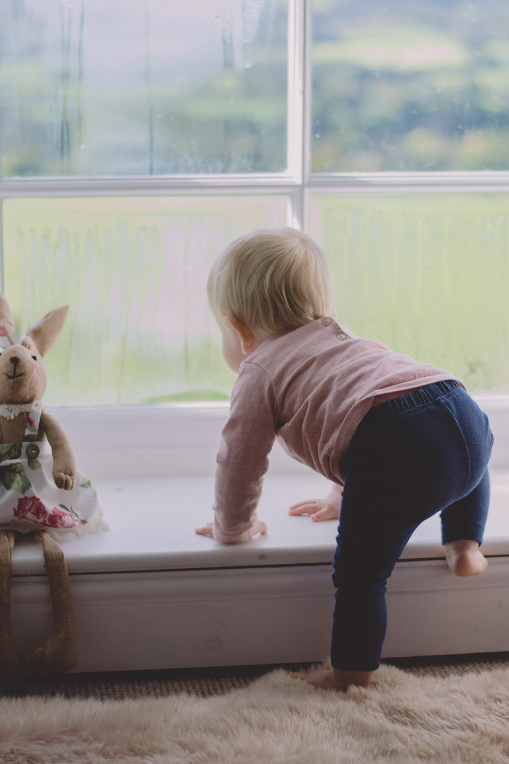 one year old girl climbs into window with bunny toy