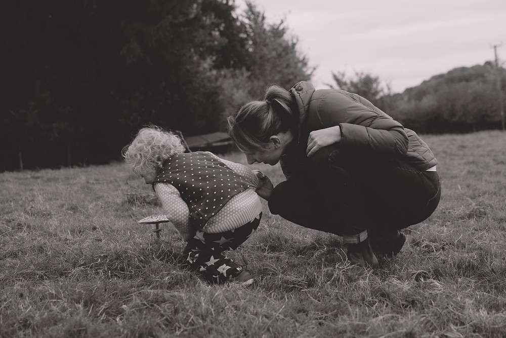 mum and toddler foraging mushrooms