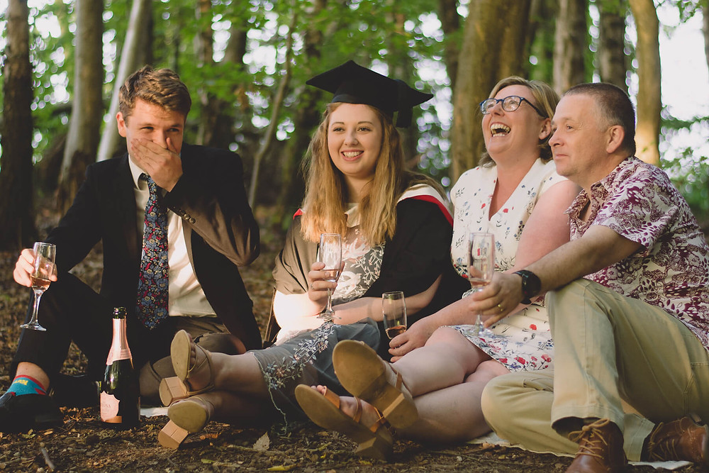 family celebrate graduation champagne in forest