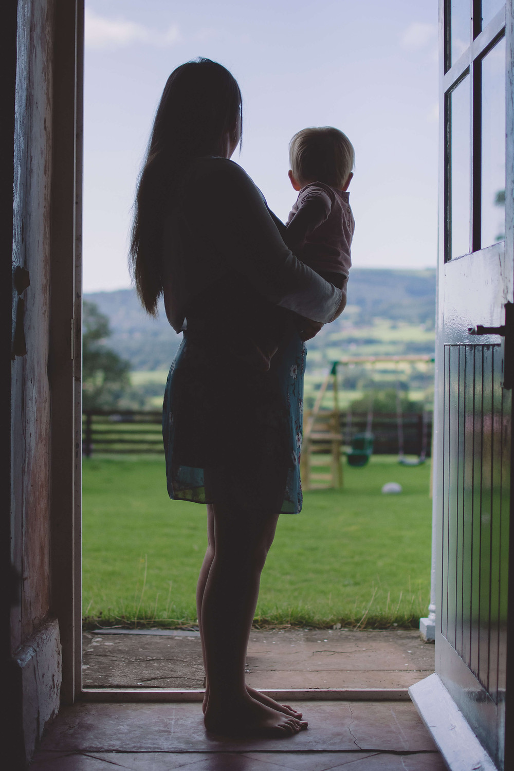 Mum and daughter cuddle looking outside