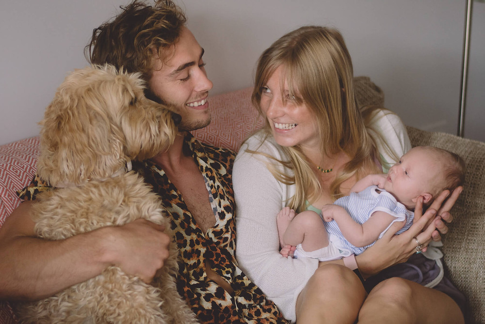 young new parents smiling baby newborn photography with dog