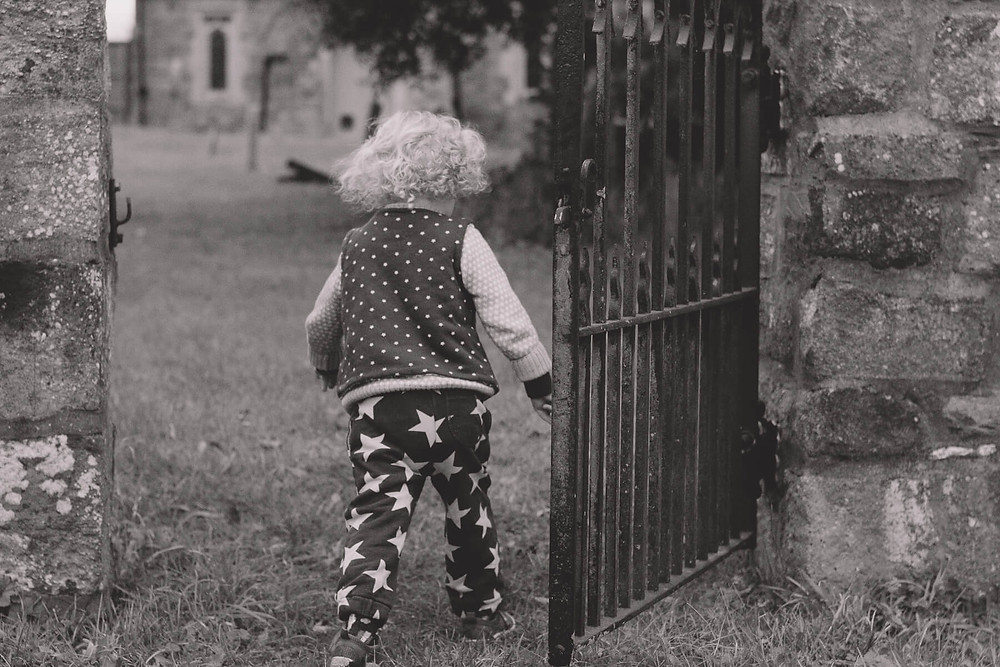 toddler walking through church yard