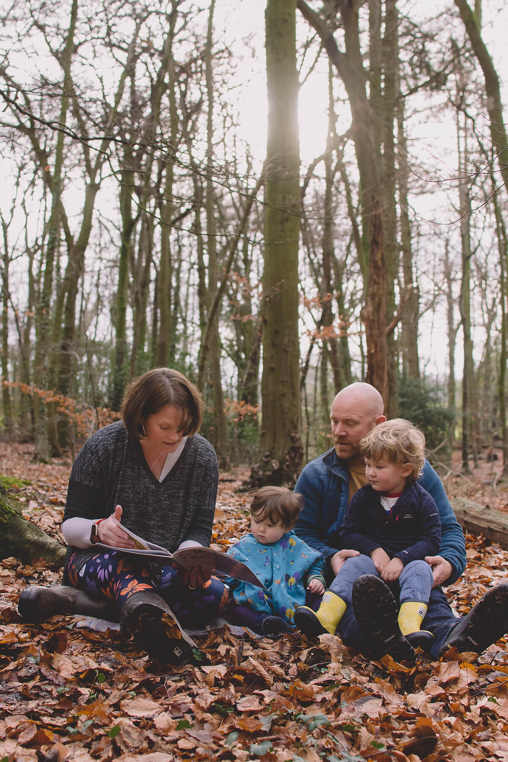 mum reading picture book to family sat in autumn forest