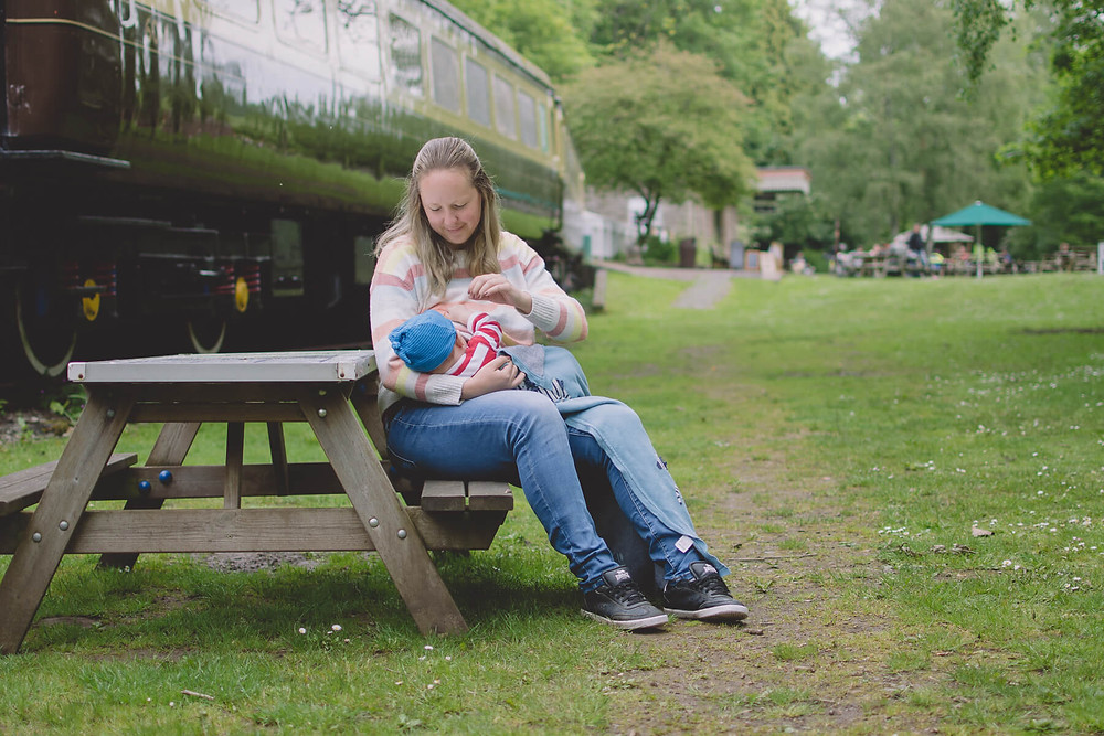 woman breastfeeding baby son outside at cafe south wales