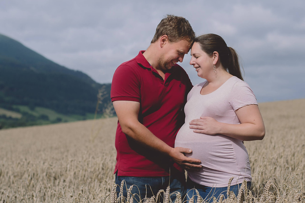 man and pregnant wife standing heads together in wheat field