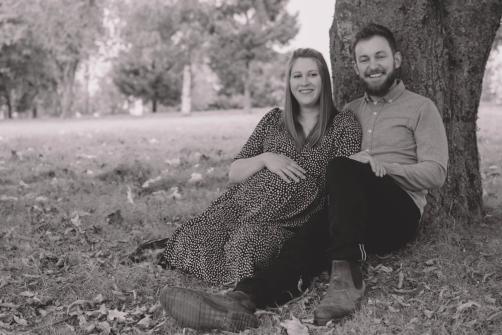 laughing pregnant couple sitting under tree
