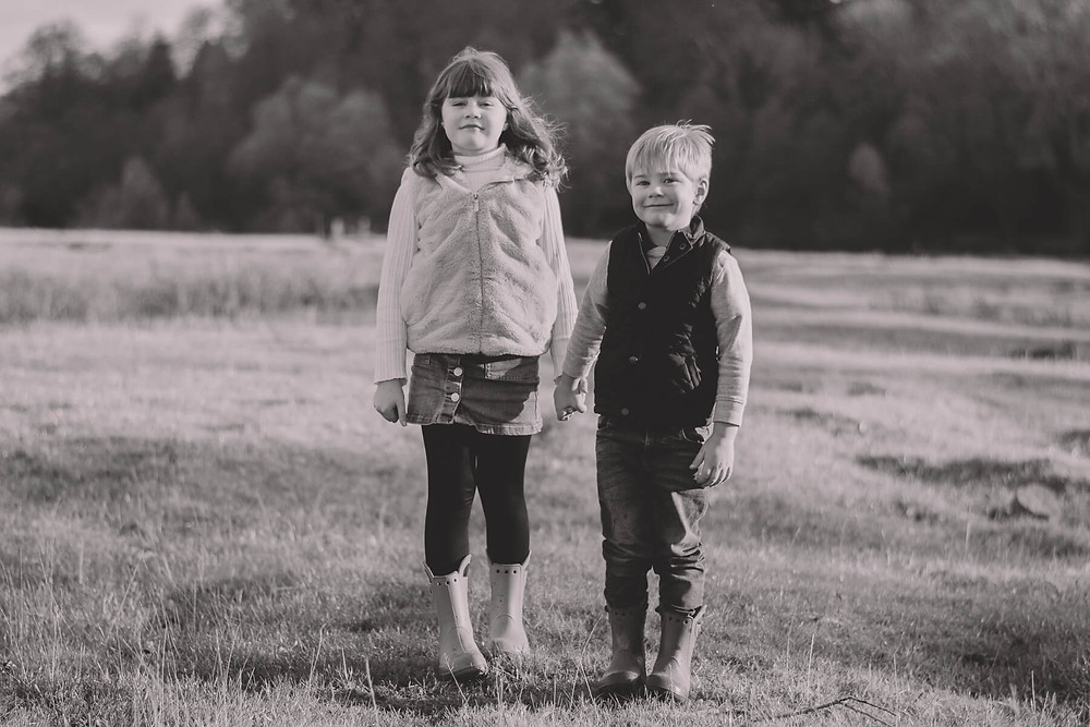 brother sister try not to smile together in field
