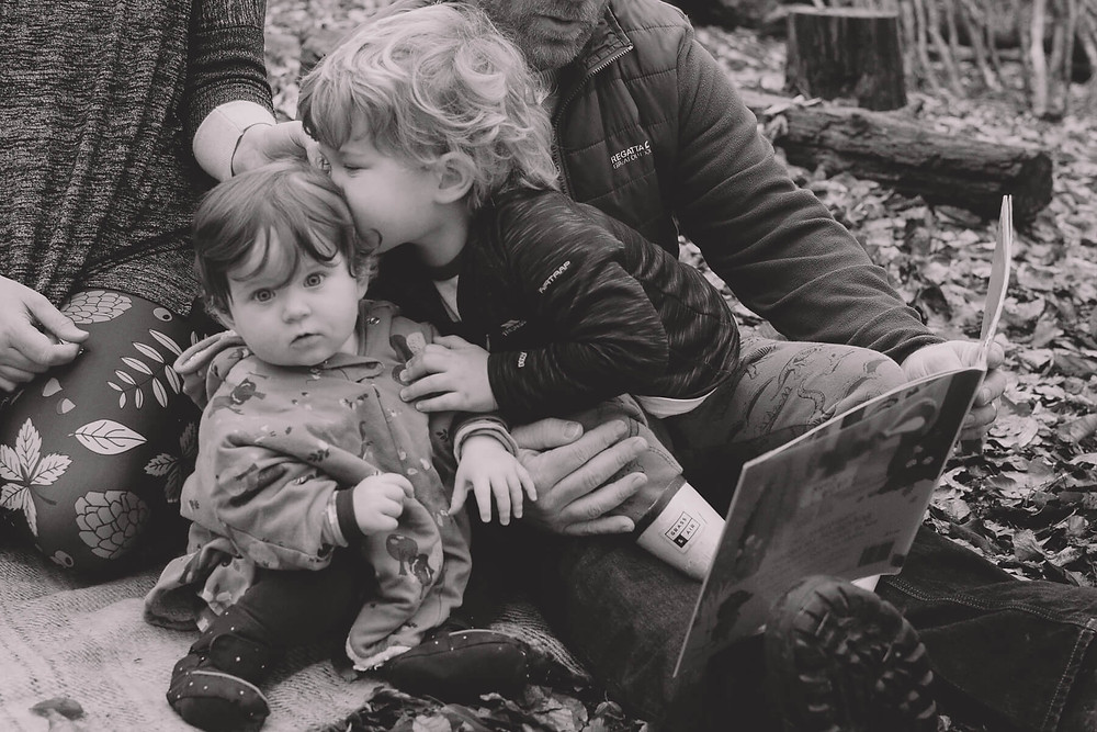 boy kisses baby sister on head black and white forest
