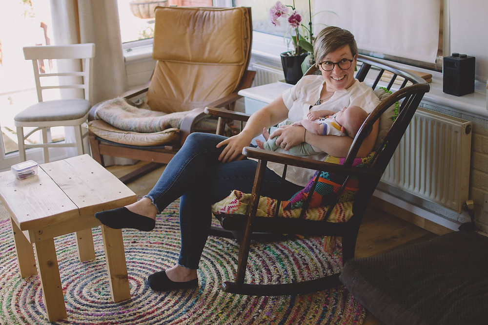 smiling mother holds newborn baby rocking chair