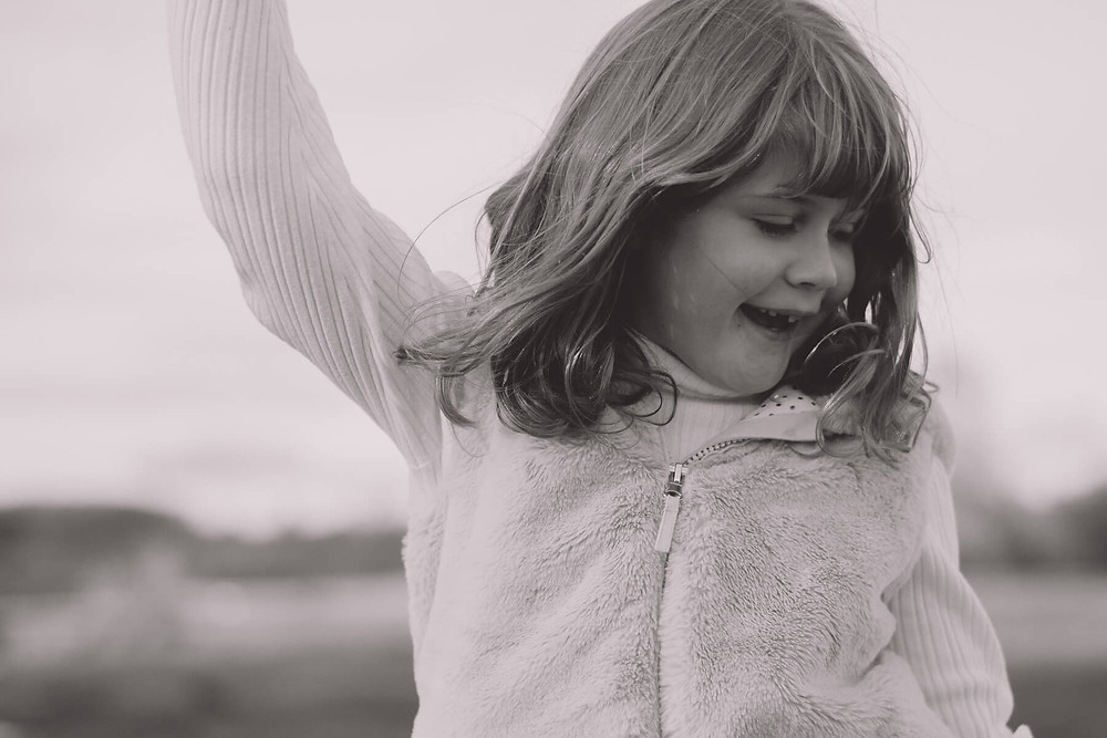 black and white young girl dancing in a field hair flying