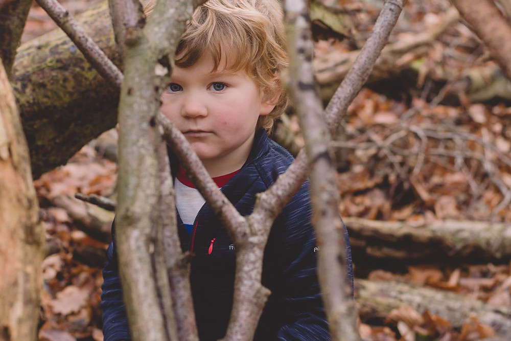 young boy playing in forest autumn leaves south wales