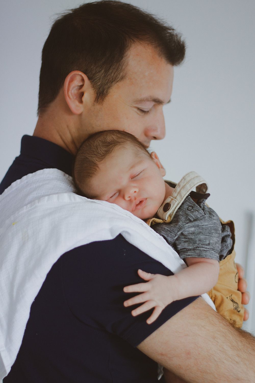 in home newborn photography baby sleeping on dads shoulder