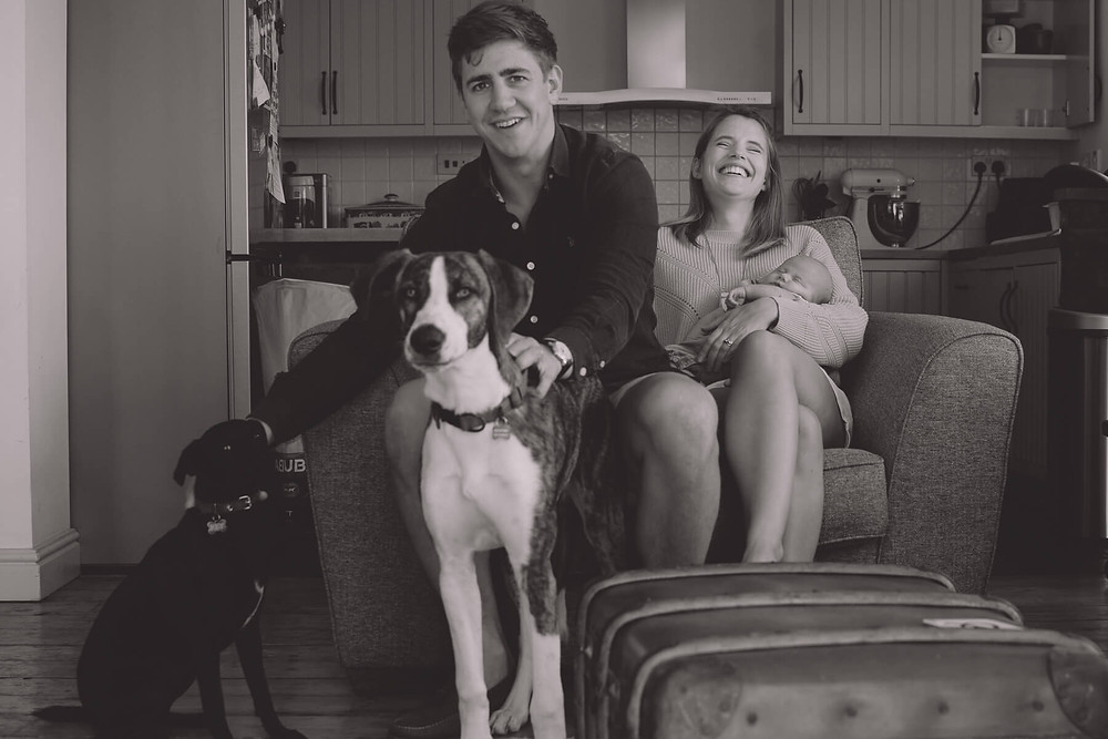 young family laughing in home with two dogs